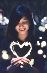 Girl draws a heart with a light